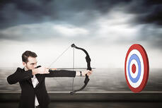 Elegant businessman shooting bow and arrow against cityscape